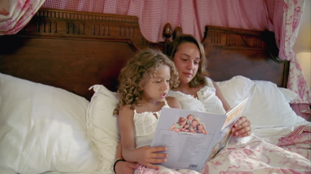 ms, teenage girl (16-17) with sister (6-7) reading book in bed, saint ferme, gironde, france - gironde stock videos and b-roll footage