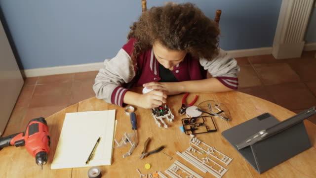 adolescente ragazza lavorando su un progetto di robotica - varsity jacket video stock e b–roll