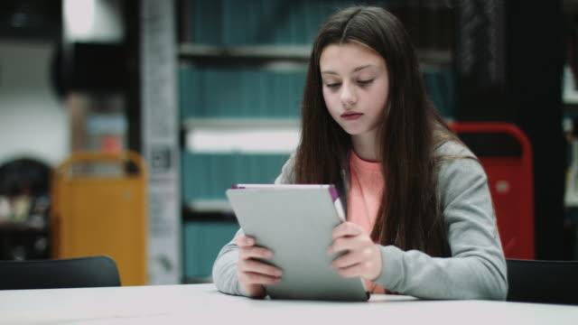 teenage girl working on digital tablet in library - endast en tonårsflicka bildbanksvideor och videomaterial från bakom kulisserna