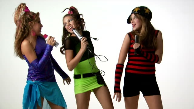 Teenage girls dancing and singing into curling iron and hairbrush