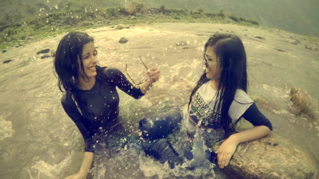 vídeos de stock e filmes b-roll de teenage girls doing fun and enjoying in river. - gota a cair na água