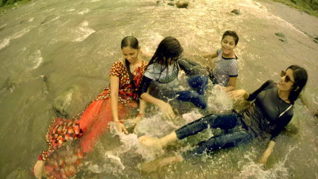 Teenage girls doing fun and enjoying in river with family.