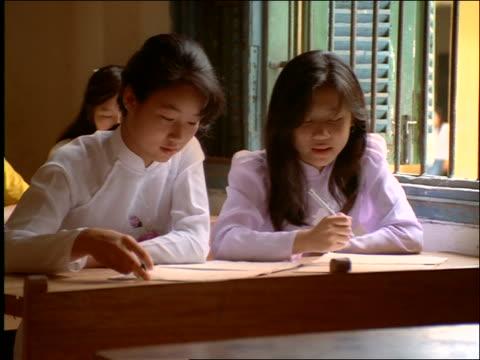 teenage girls doing schoolwork in classroom / vietnam - solo adolescenti femmine video stock e b–roll