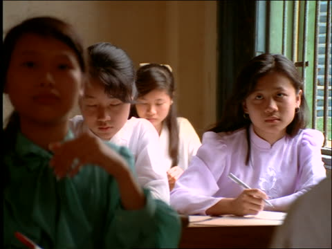 Teenage girls doing schoolwork in classroom / Vietnam