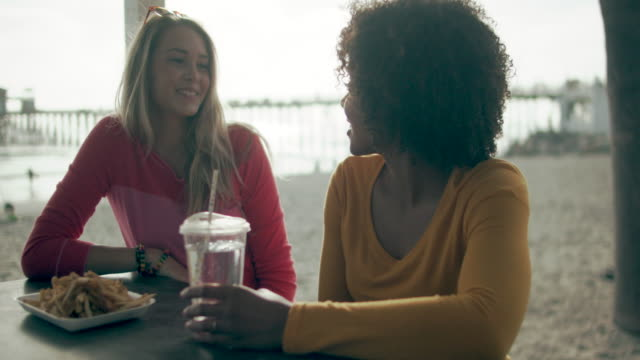 ms teenage girls eating french fries at the beach - zwischenmahlzeit stock-videos und b-roll-filmmaterial