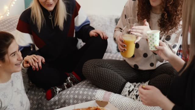 teenage girls eating pizza at sleepover christmas party - slumber party stock videos and b-roll footage