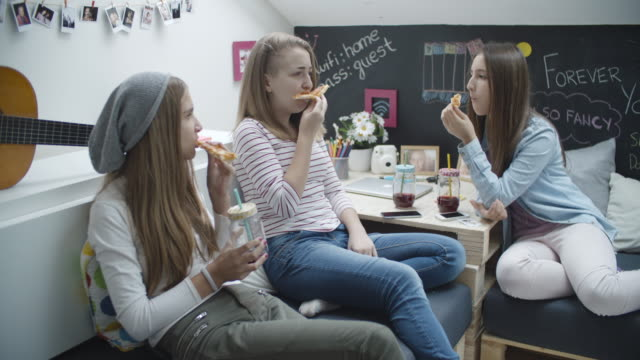 4k: teenage girls eating pizza. - slumber party stock videos and b-roll footage