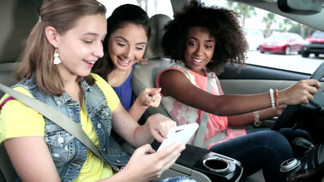 teenage girls in car looking at mobile phone, talking - teenagers only stock videos & royalty-free footage