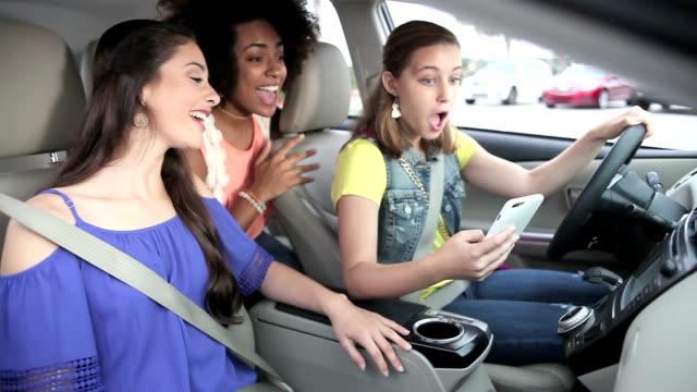 Teenage girls in car looking at mobile phone, talking