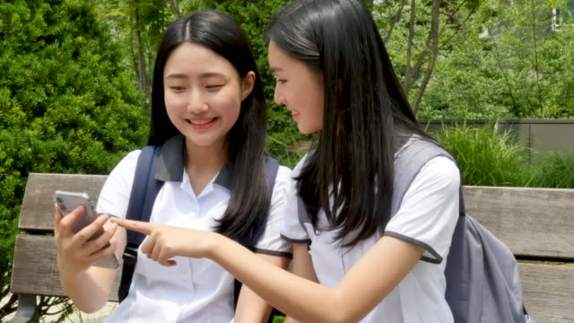teenage girls in school uniform talking together on the bench - uniform stock videos & royalty-free footage