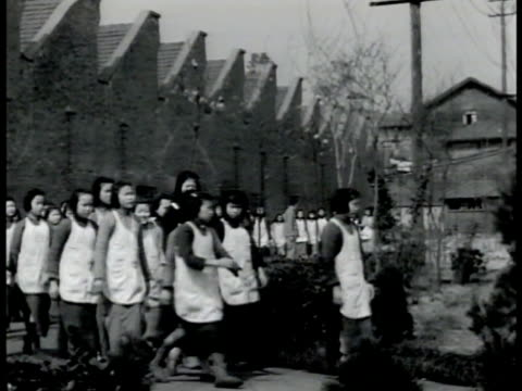 Teenage girls in uniform dress apron walking to textile mill HA WS Girls young women working at machines in cotton mill MS Young adult females...