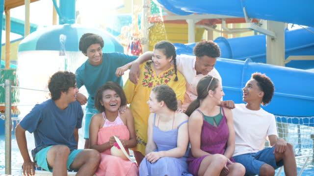 teenager-mädchen von teenager-jungs im wasserpark begleitet - multi ethnic group stock-videos und b-roll-filmmaterial