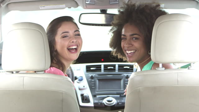 teenage girls laughing in front seats of car - learning to drive stock videos & royalty-free footage