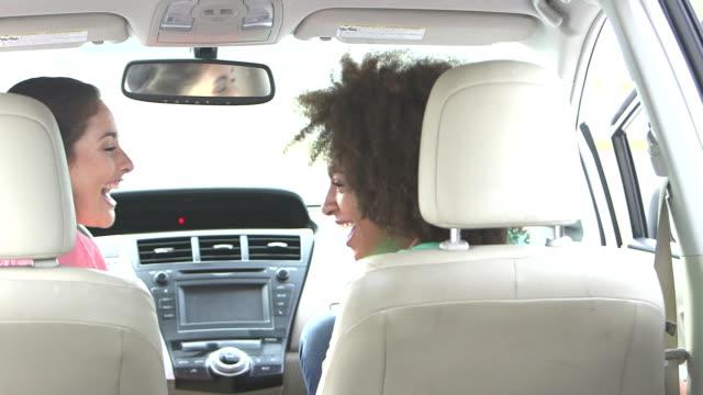 Mädchen im Teenageralter lachen vorne Sitze des Autos