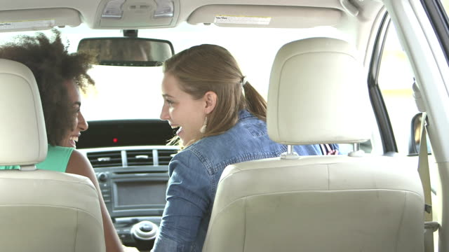 teenage girls laughing in front seats of car - entering stock videos & royalty-free footage