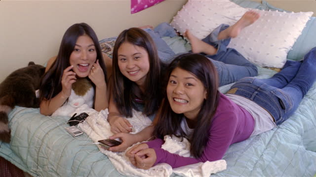 Teenage girls listening to MP3 players on bed smiling up at camera / Arizona