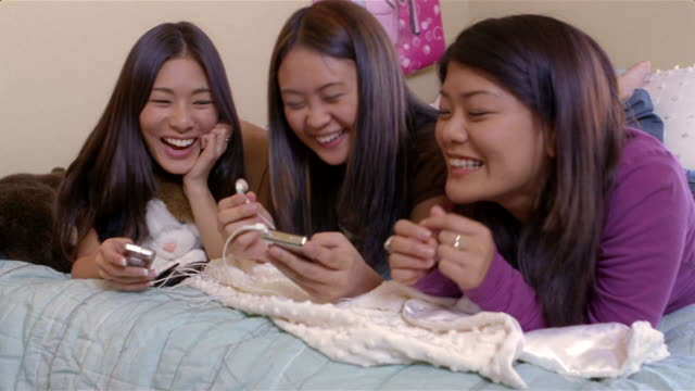 teenage girls lying on bed listening to music or watching podcast on mp3 player / arizona - listening stock videos & royalty-free footage