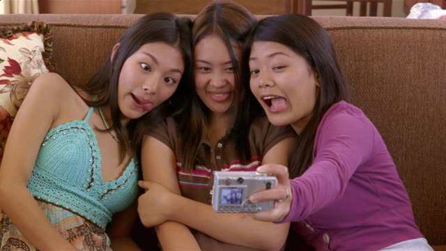 teenage girls making faces while taking photos of themselves with digital camera / looking at picture and laughing / arizona - pulling funny faces stock videos & royalty-free footage