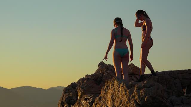 日没時にアドリア海に飛び込む高い崖の上の十代の女の子 - アドレナリン点の映像素材/bロール