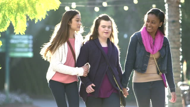 teenage girls, one with down syndrome, walking in park - 14 15 years stock videos & royalty-free footage