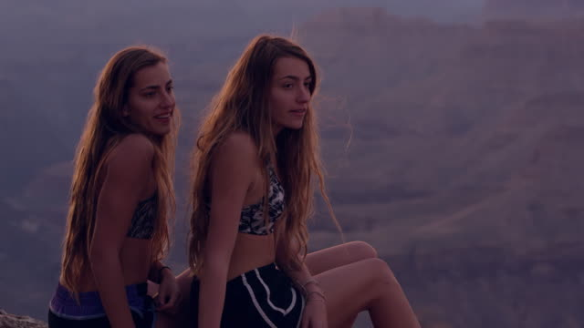 Teenage girls overlooking Grand Canyon at Dusk and leaving edge