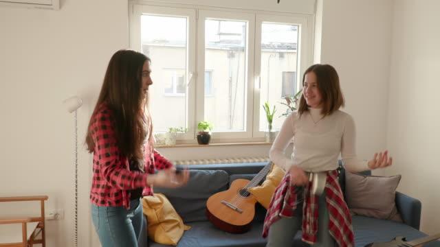 vidéos et rushes de adolescentes jouant des guitares d'air et riant dans le salon - guitare imaginaire
