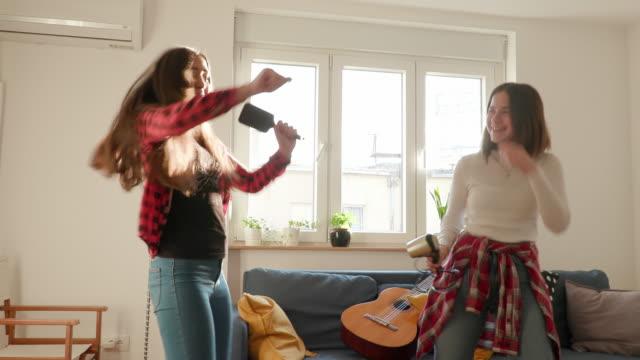 vidéos et rushes de adolescentes jouant des guitares d'air et chantant dans le salon - guitare imaginaire