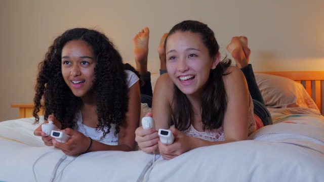 Teenage girls playing video games on bed