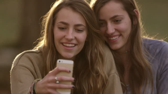 teenage girls posing of photos they are taking with smartphone - twin stock videos & royalty-free footage
