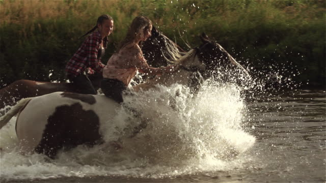 teenage girls reiten horse river splash freiheit superslow bewegung 4k - pferderitt stock-videos und b-roll-filmmaterial