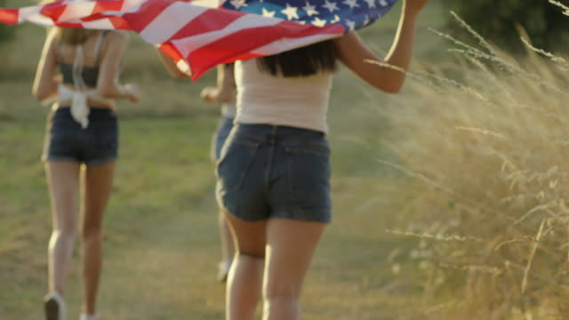 Teenage girls running with American Flag celebrating Independence Day