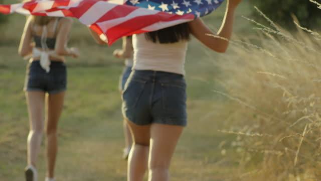 独立記念日を祝う米国の旗と実行している 10 代の少女