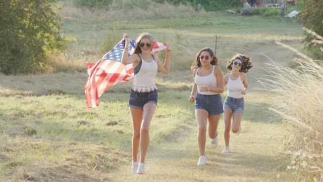 Teenage girls running with an American flag