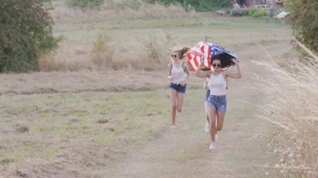 teenage girls running with an american flag - fatcamera stock videos & royalty-free footage