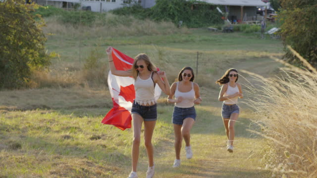 Teenage girls running with Canadian Flag celebrating Independence