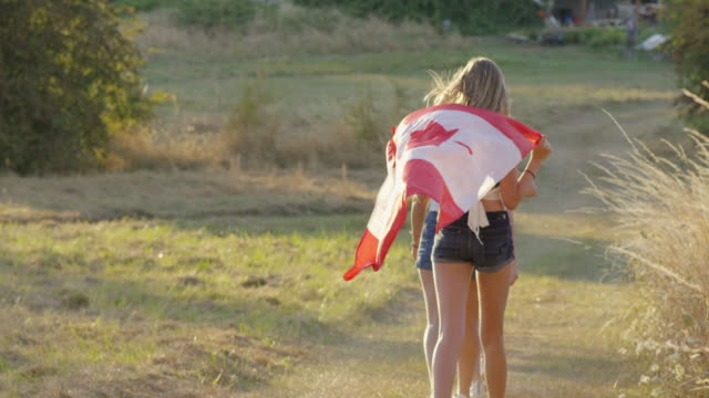teenage girls running with canadian flag celebrating independence - bandiera del canada video stock e b–roll