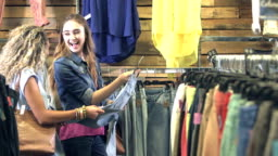 Teenage girls shopping for jeans in clothing store