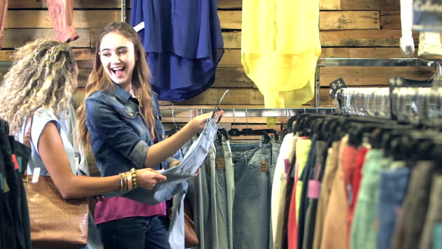 vídeos de stock e filmes b-roll de teenage girls shopping for jeans in clothing store - mercadoria