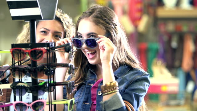 teenage girls shopping for sunglasses in clothing store - teenage girls stock videos & royalty-free footage