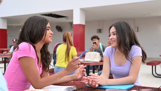 vidéos et rushes de adolescentes s'asseyant et parlant à la table extérieure - niveau collège lycée