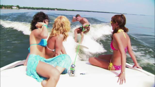 ms teenage girls sitting on back of motorboat as it pulls wakeboarder on lake/ texas - ビキニ点の映像素材/bロール