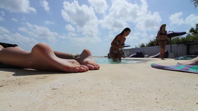 ms slo mo teenage girls sunbake and swimming in infinity pool / padang padang, bali, indonesia - barefoot stock videos & royalty-free footage