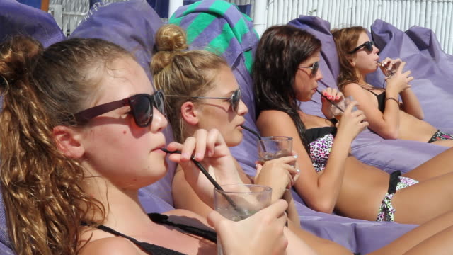 MS Teenage girls sunbaking and drinking in sun / Padang Padang, Bali, Indonesia