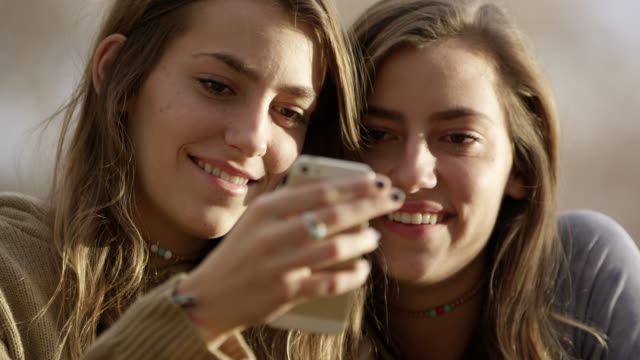 teenage girls swiping on smartphone they are looking at - handhaben stock-videos und b-roll-filmmaterial