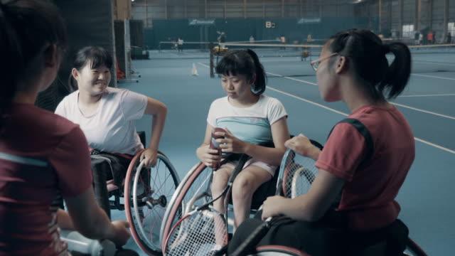 teenage girls taking a break from playing wheelchair tennis - 身体障害点の映像素材/bロール