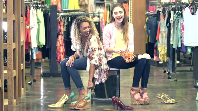 teenage girls trying on shoes in clothing store - footwear stock videos and b-roll footage