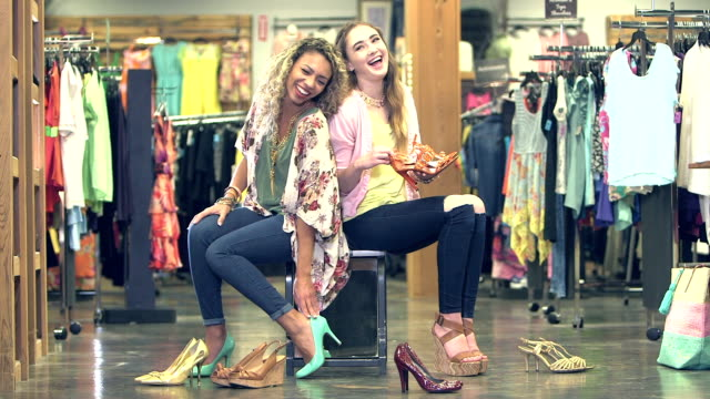 vídeos de stock e filmes b-roll de teenage girls trying on shoes in clothing store - sandália