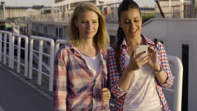 Teenage girls using smart phones in the city