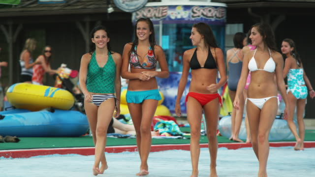 vídeos de stock, filmes e b-roll de teenage girls walking through a water park - biquíni