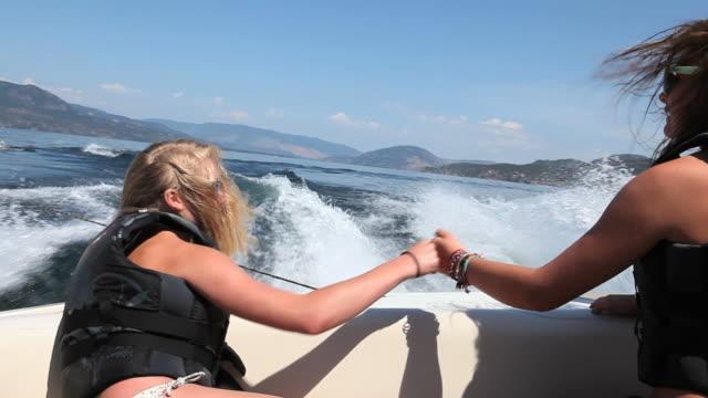 POV, teenage girls watch friends tubing behind boat